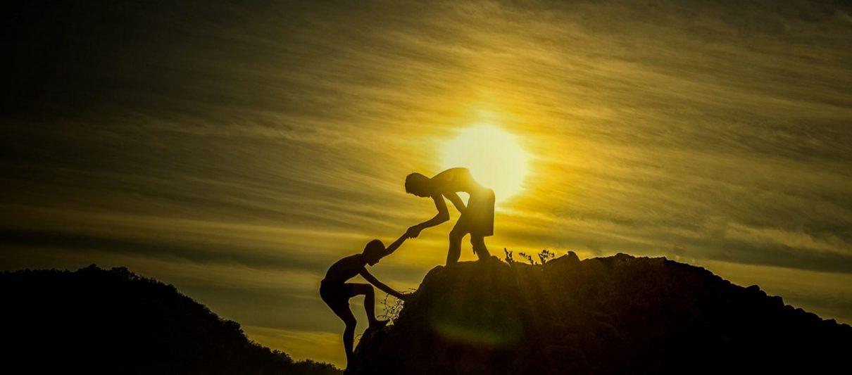 Deux humains monte une montagne avec le soleil couchant